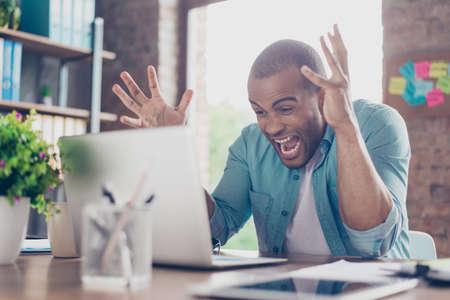 仕事で気が狂いました。ムラートの若い起業家は彼が叫んでいると、狂ったように身振りで示す、彼はビジネス、失敗のショックを受けて 写真素材