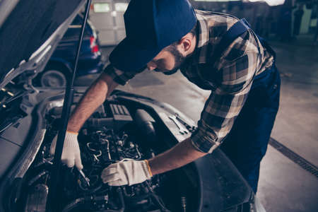 Close up of young bearded expert specialist appraising the damage for repairing car at work shop, mounting it, arms in white knitted gloves, hat and special blue uniform overall, ckeckered shirt Stock Photo