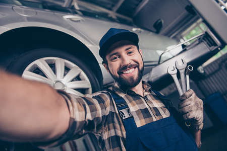 Attractive brunet bearded automotive expert with beaming smile makesphoto with metal mechanical keys in arm, in special safety outfit uniform, checkered shirt, hat head lifted up vehicle behind Stok Fotoğraf - 88128161