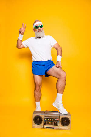 Crazy aged serious athlete pensioner grandpa in eyewear, sneakers, shorts, with bass clipping ghetto blaster recorder. Old school, swag, fooling around, gym, workout, technology