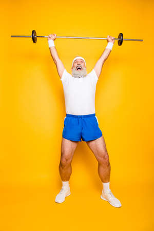 Full length of confident cool funny insane emotional active grandpa with  win victory grimace, exercising training, holding equipment, lifts it up, wears sexy shorts, sneakers, yell shout
