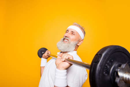 Comic, confident cool grey haired grandpa with humor grimace exercising holding equipment, lifts it up. Body care, hobby, weight loss, deadlift, powerlifting, pressure, proud lifestyle Stock Photo