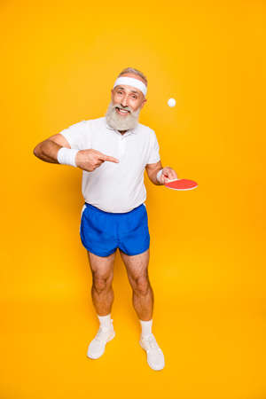 Healthcare, weight loss, bodycare lifestyle. Competetive emotional cool active goofy comic grey haired grandpa with humor grimace and beaming grin, with table tennis equipment, plays it