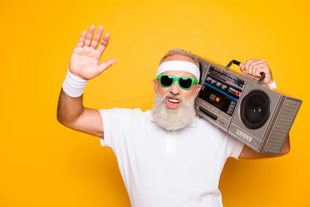 Cheerful excited aged funny gangster cool grandpa dude in eyewear with bass clipping ghetto blaster recorder. Old school, swag, fooling, gym, technology, success, hip hop