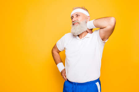 Frustrated pensioner grandpa with funny grimace is having a strong pain in nape. Bodycare, healthcare, injury, aging, symptom, therapy, salve, treatment, hurt, disorder, workout, weight loss lifestyle