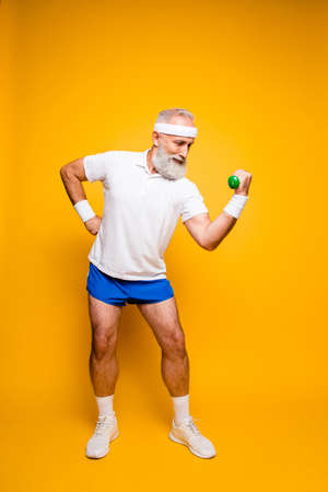 Cool grandpa with confident grimace exercising holding equipment up, lifts it with strength and power, wearing blue sexy shorts. Body care, hobby, weight loss,  lifestyle