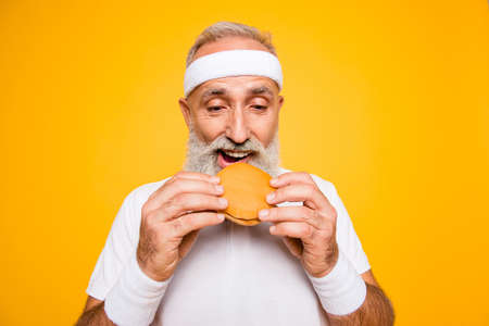 Close up of modern athlete cool grey haired pensioner grandpa hold yummy tasty delicious heavy grossy sandwich, destroys it. Weightloss, healthcare, gym, strength, regime, challenge lifestyle