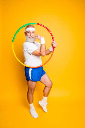 Cheerful cool excited crazy funny fooling playful gymnast grandpa with comic grimace shows off with hoolahoop, demonstrating his bicep. Body care, hobby, weight loss