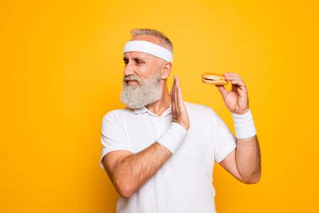 Ernstige strenge ruwe coole atleet houdt sandwich, waarschuwing met arm Stockfoto