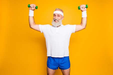 Gracieux papy cool avec l'humour grimace exerçant la tenue de l'équipement, soulève avec force et puissance, portant des shorts sexy bleus, si chaud! Banque d'images - 88218137