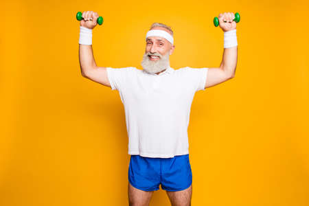 Cheerful cool grandpa with humor grimace exercising holding equipment up, lifts it with strength and power, wearing blue sexy shorts, so hot!
