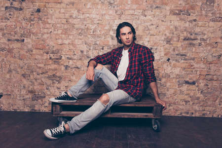 Full length of young successful freelancer student on the brick stones wall background, sitting on top of palette, in casual checkered outfit, jeans, sporty casual shoes Stock Photo