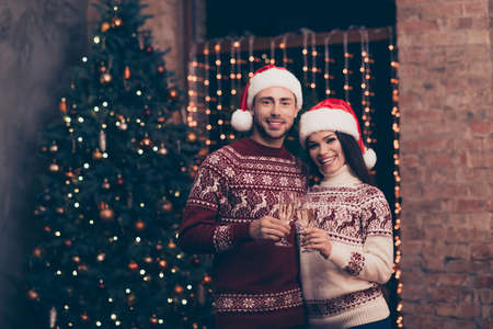 Festive friends with stemware of martini embrace bonding, so excited in knitted cute traditional x mas costumes with ornament, headwear, jeans, enjoy, december time, firtree, garland, night