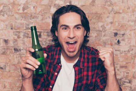 Men`s life. Close up cropped portrait of amazed brunet hipster with bristle in casual outfit is excited watching the game at holiday, having drink, joyful grimace, gesturing victory with fists