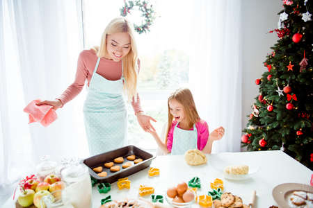 Amazed cute blonde mum and small girl in arpons made sweet tasty yummy treats, table top with lots of bakeware, ingridients, apples, green and yellow form cutters, flour. Bakery, learn, teach concept Stock Photo