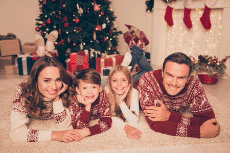 Four cheerful beautiful bonding relatives, at home, married couple of brunet and brunette haired, excited siblings, in knitted cute traditional x mas costumes, in socks, noel is here!