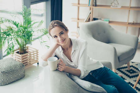 Cute brown haired gorgeous freelancer on the beige couch at home having hot beverage, looking in camera, so comfortable, in smart fashioanble outfit, with fashionable hairdo Stock Photo