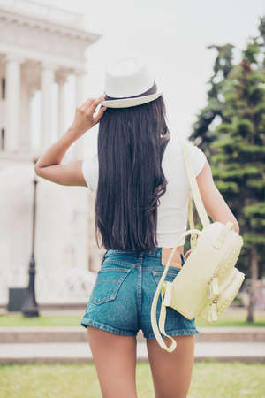 Back shot of mixed-race lady`s butt in tight short denim shorts on town`s background. Nice smooth bronze skin, beige cap headwear, long hair, yellow rucksack. She is on the stroll outside