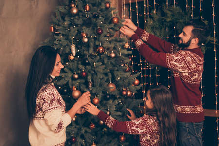 Three relatives at home in knitted traditional costumes, ready to celebrate christmastime, x mas eve. Happiness, friendship, parenthood, childhood, upbringing, unity, mother, father