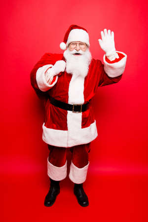 Full length of funny santa in headwear, costume, black belt, white gloves, waves with arm palm, brings gifts for kids, ready, prepared