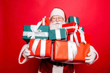 Festive seosonal occasion. Holly jolly x mas! Funny excited friendly generous santa`s face is popping up of gifts, he is presenting, red traditional fur coat, isolated on red background Stock Photo