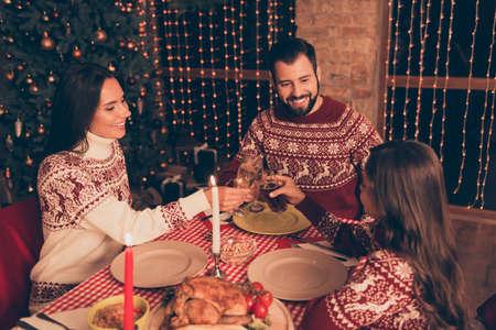 Three beautiful cheerful gathered relatives, setted desktop, full of yummy treats, married couple, girl, in knitted traditional x mas costumes, decorated room Stock Photo