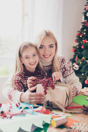 Childhood, hobby, x mas, noel, happiness, upbringing, leisure, friendship, concept. Little lovely blonde with her mom are organising design of gift, enjoying using rope, ribbon, tape, firtree near