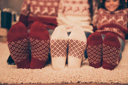 Close up cropped low angle of focus on three pairs of feet of festive husband and wife, baby girl, sitting down on floor, winter december feast x mas noel at coziness, in socks