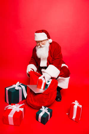 Holly jolly x mas noel time! Funny santa in headwear, costume, black belt, shoes, white gloves fills sack with a lot of gifts for kids, with ribbon tapes bows, digital devices