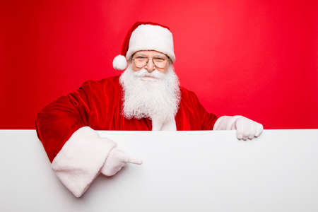 Advertisement, discounts, presents gifts selling december, winter tradition wish, celebration of christmastime  concept. Santa is standing behind the white blank banner and points at side, empty