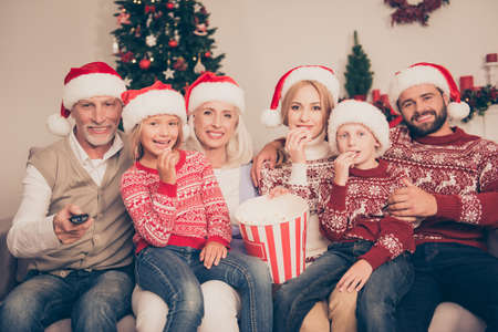 Multi generation, happiness, friendship. Group of cheerful relatives bonding on couch, excited, mom, dad, siblings, grandad, granny, in knitted cute traditional x mas costumes, firtree, home, movie Stock Photo