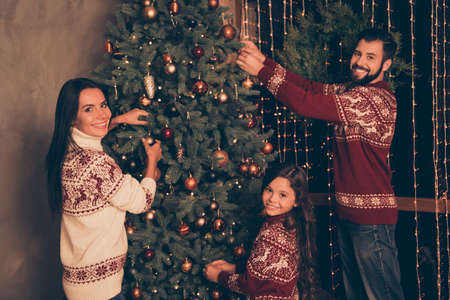 Ready to celebrate christmastime, x mas eve. Three relatives at home in knitted traditional costumes. Happiness, friendship, parenthood, childhood, upbringing, unity, mother, father