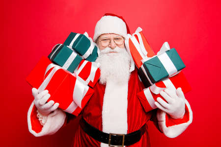 Festive seosonal occasion. Funny excited positive friendly generous santa in red traditional fur coat presenting gifts, isolated on red background, wishing happiness Stock Photo