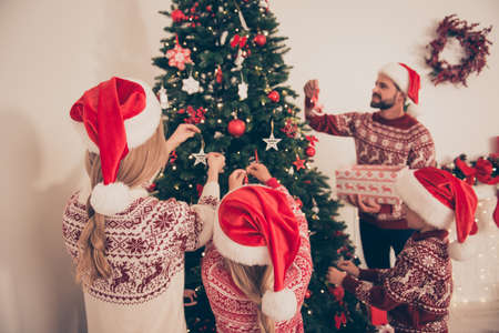 Four relatives at home, married couple, siblings in knitted traditional costumes, prepare to celebrate x mas. Happiness, friendship, parenthood, childhood, upbringing, unity