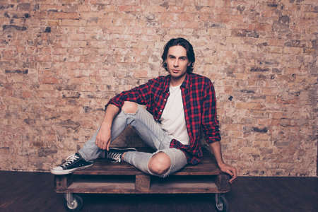 Full length close up of young successful freelancer student on the brick stones wall background, sitting on top of palette, in casual checkered outfit, jeans, sporty casual shoes