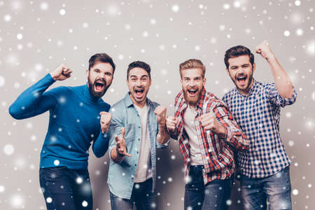 Four cheerful young men are standing and gesturing for the victory on snowflakes wall in casual outfit and jeans. They are fans of sports games as football, basketball, hockey, baseball