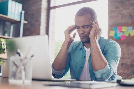 Overwerkt gestresste mulat freelancer heeft hoofdpijn en denkt aan het einde van een project. Hij zit in een informele smart, op zijn thuiskantoor