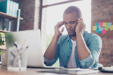 Overworked stressed mulatto freelancer is having headache and thinking how to end project. He is in a casual smart, at his home office