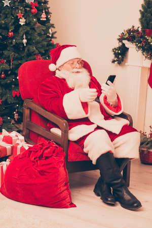 Holly jolly x mas, noel is snel! Geconcentreerde peinzende kerstman denkt, bestudeert een lijst met kinderwensen en geschenken op pda, klaar om dromen waar te maken, geluk brengen aan kinderen Stockfoto - 89427297