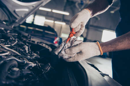 Close up cropped shot of experts mechanical specialist professional checking oil level in car engine with orange tool, in repair shop. Maintenance, safety, open supported hood of auto Stock Photo - 89427394