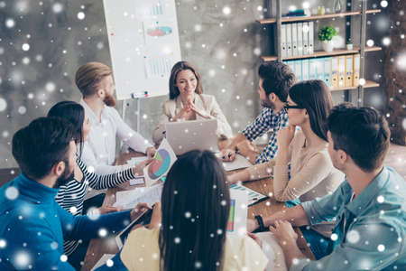 Young beautiful lady is reporting to the team about the development of the company at the meeting. Collegues are listening to her with attention, snowflakes winter background