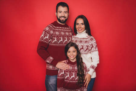 Holly molly x mas time! Three cheerful beautiful relatives, married couple of brunet and brunette haired, excited girl with mom and dad, in knitted cute traditional x mas costumes posing cuddling Stock Photo