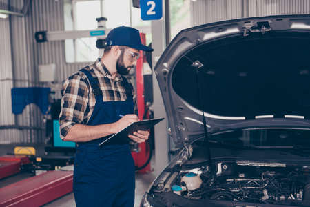 Expert professional engineer at mechanical work shop, in special safety outfit uniform, checkered shirt, hat head wear, filling the form of automotive breakdown, focused, serious, concentrated