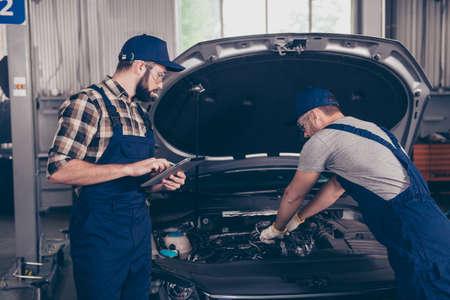 Deux experts en mécanique travaillant à l'atelier, vêtus de l'uniforme de sécurité bleu spécial, coiffe de chapeau avec dispositif PDA, connexion Internet, contrôle, inspection, assistance Banque d'images - 89628923