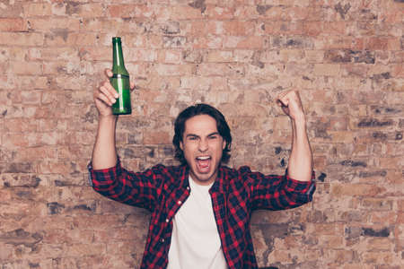 Men`s life. Amazed brunet hipster freelancer with bristle in casual outfit is excited watching the game at holiday, having drink, joyful grimace, gesturing victory with fists of hands