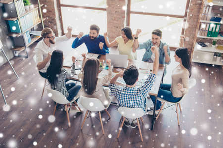 Success and team work concept. Top up of team of business partners with raised up hands in light modern workstation, celebrating the growth of their company, snowflakes background