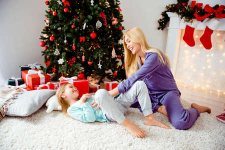Attractive mom with small little lovely cheerful girl fooling around in sleep wear, barefoot on carpet near fir pine tree, she tickles belly of baby. Maternity, motherhood, emotions, childhood