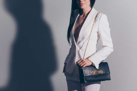 Cropped shot of hot gorgeous well dressed by formal dress code stunning charming business lady, standing on pure light background, with arm in pockets of classic pants, other on cool dark bag Stock Photo