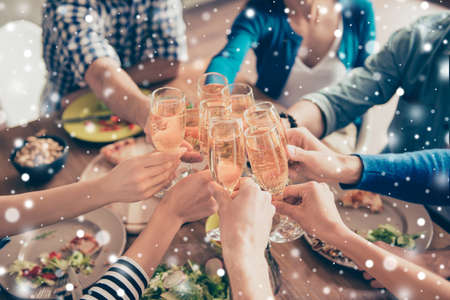 Cropped close up photo of glasses with champagne. Young people are toasting to celebrate the event, enjoying xmas winter vacation. Table is full of tasty food and drinks, snowflakes background Stock Photo