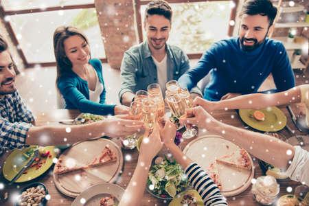 Hoge hoekmening van vrienden bij de rammelende glazen van de verjaardagspartij met champagne en het roosteren, genietend van de vakantie van de Kerstmiswinter, smakelijke schotels op de lijst, sneeuwvlokkenachtergrond Stockfoto